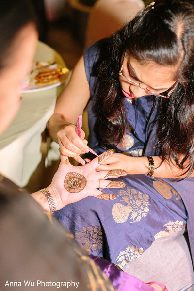 Indian mehndi artist doing  hand henna decorations.