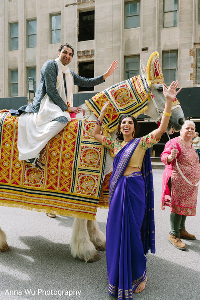 Indian groom with relatives at baraat celebration.