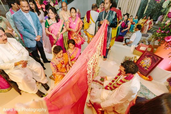 Indian bride and groom separated by antarpat.