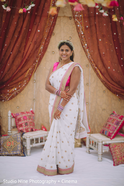 Indian bride in her white pink and golden sari.
