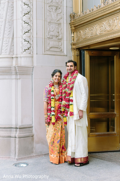 Indina bride and groom possing with their red and yellow garlands.