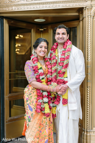 Indian couple in their ceremony orange saree and white kurta.