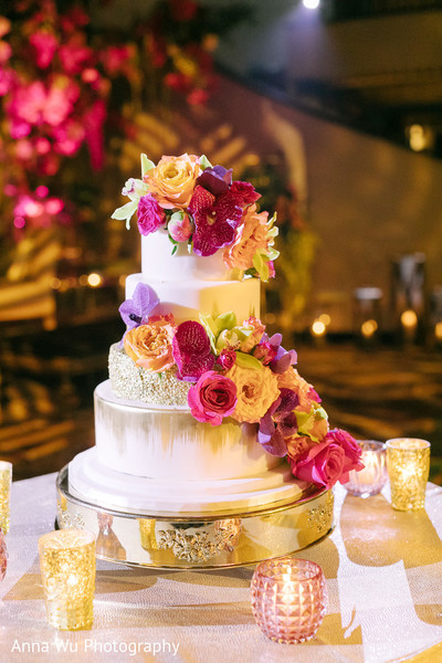 white and golden with roses Indian wedding cake .