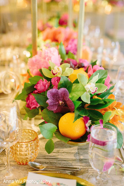Orchid flowers with orange in Indian wedding table centerpiece.