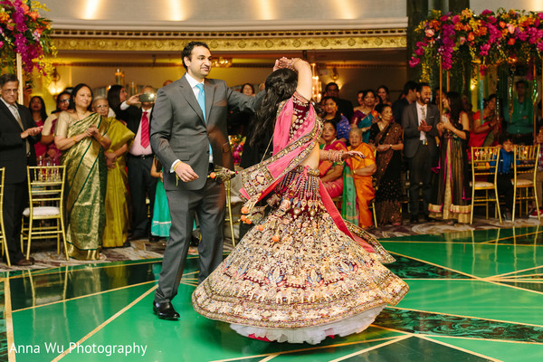 Indian bride and groom dancing on the green dance floor.