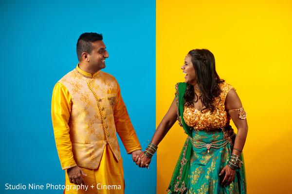 Maharani and raja in their yellow and aqua sangeet outfits.