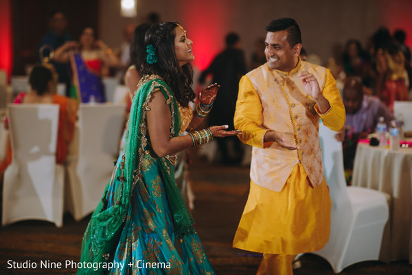 Indian couple dancing at sangeet party.