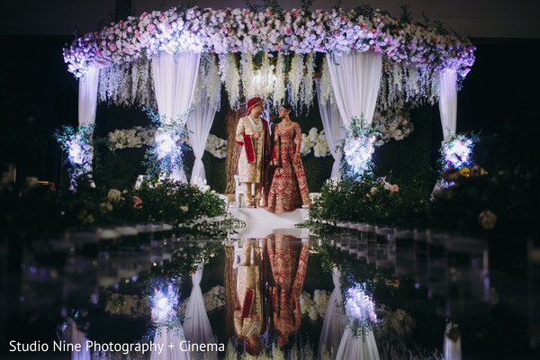 Indian bride and groom posing under ceremony white mandap.