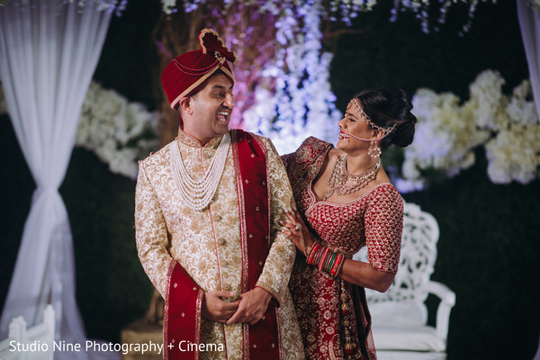 Indian couple smiling at ceremony mandap.