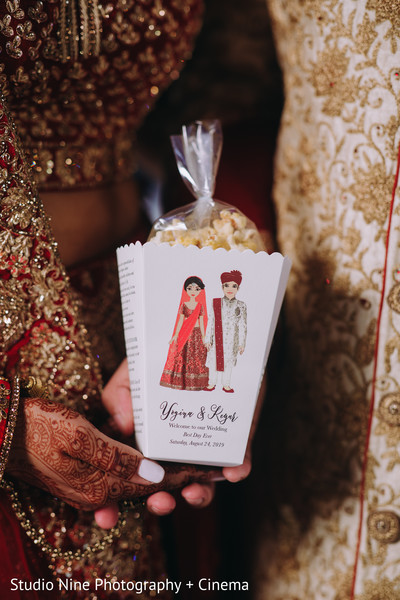 Indian couple holding popcorn favor box.