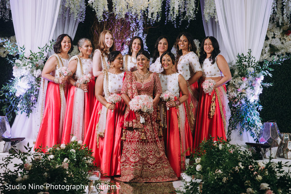 Indian bride posing at mandap with bridesmaids.