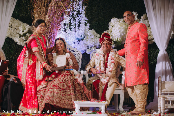 Indian couple with relatives at white mandap.