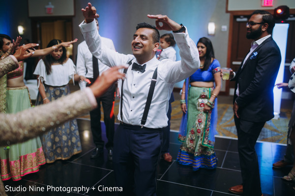 Indian groom dancing with bridesmaids.