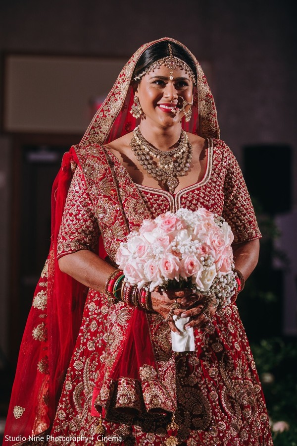 Indian bride making her entrance in her red lehenga.