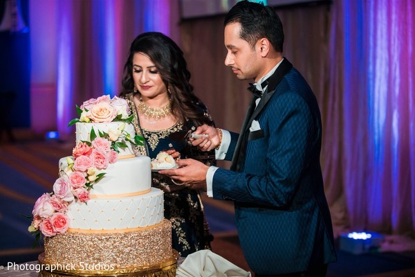 Indian couple cutting whiten and golden wedding cake.