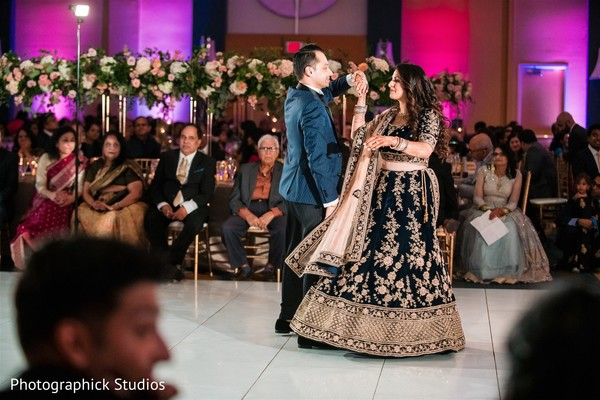 Indian bride dancing with groom at reception.