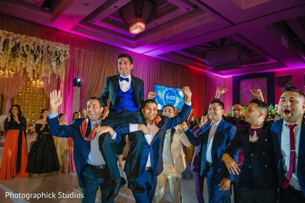 Indian groom lifted by groomsmen at reception.