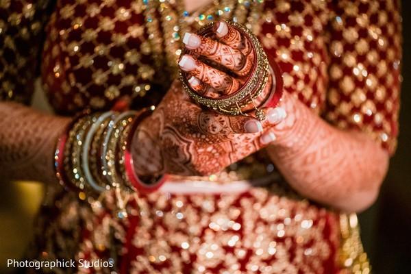Indian bride putting on her wedding braceletes .