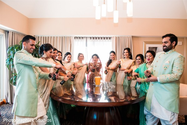 Indian bride with bridesmaids and groomsmen popping bottles.