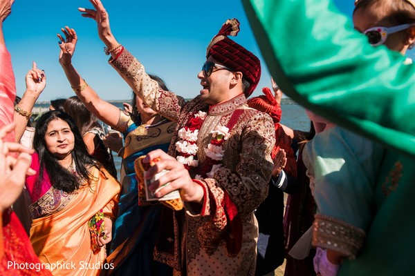 Indian groom holding coconut at baraat.