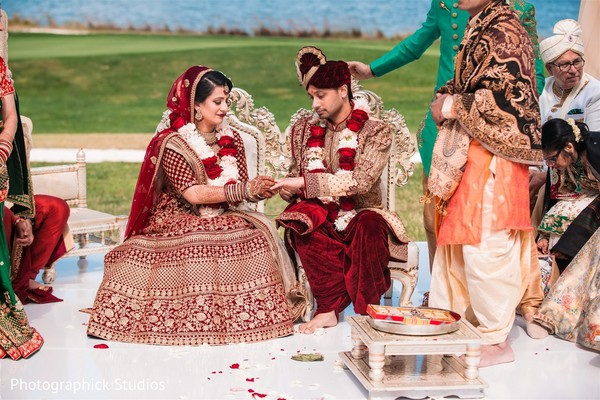 Indian bride putting ring to groom at wedding ceremony.