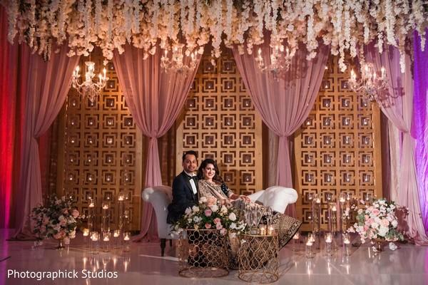 Indain couple posing at reception mandap.