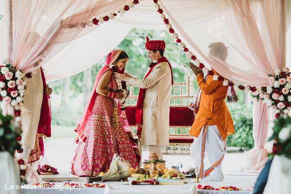 Indian groom putting the jaimala to bride.
