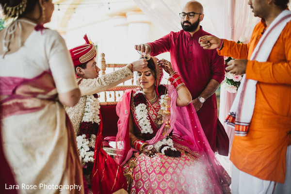 Indian groom putting the red dot on maharani's forehead.