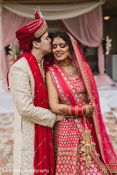 Indian couple posing with ceremony outfits.
