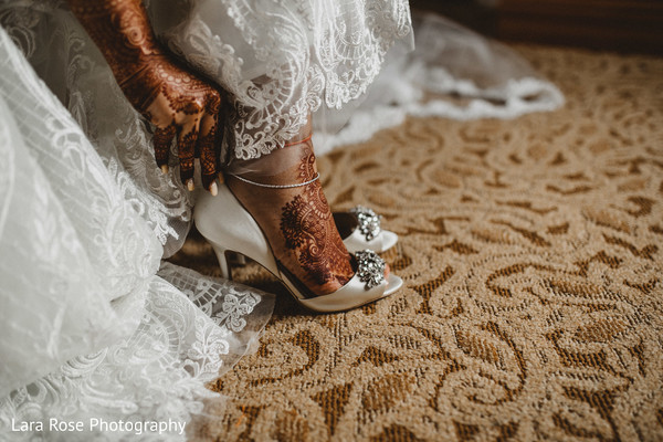 Indian bride putting her white wedding shoes.