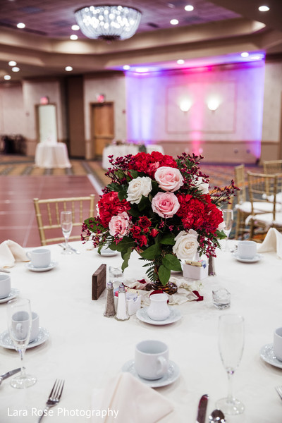 Indian wedding table pink roses and red flowers decoration.