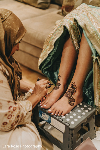 Indian bride getting her mehndi art on feet.
