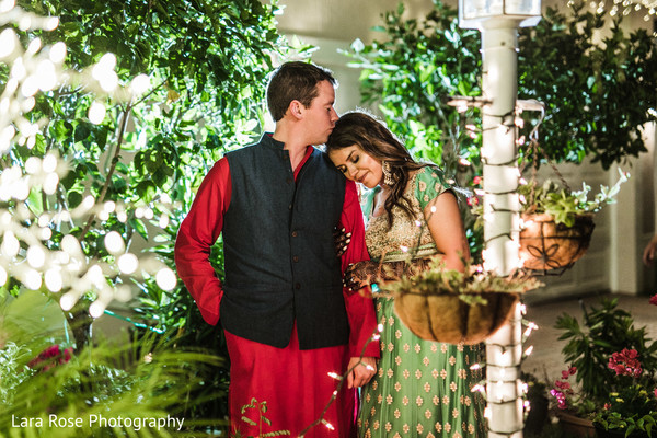 Indian couple posing outdoors in their sangeet outfits.