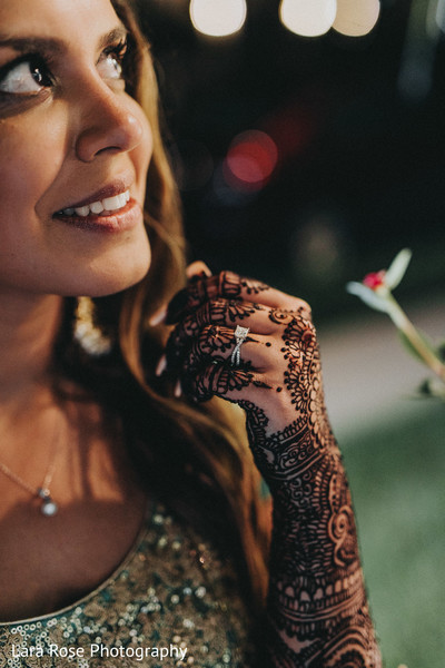 Indian bride with her white gold ring in her mehndi decorated hand.