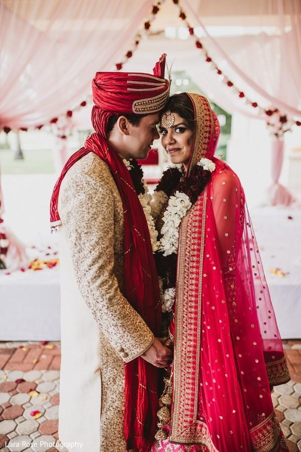 Indian bride and groom posing at mandap.