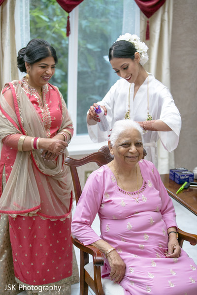 Indian bride fixing relative's hair.