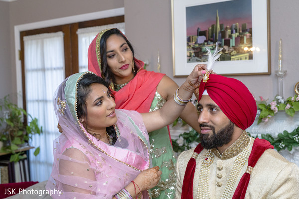 Indian groom getting his Sarpech on red turban.