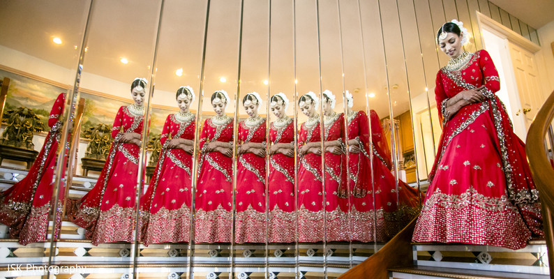 Indian bride walking down the stairs with red lehenga.