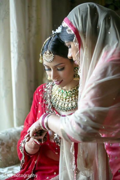 Indian bride putting on her red bangles.