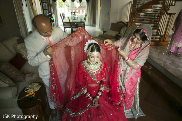Indian bride's relatives putting her ghoonghat on.