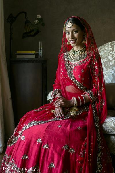 Maharani posing with her ceremony red lehenga and her jewelry.
