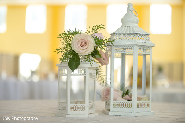 Light pink roses with white lanterns indian wedding table decoration.