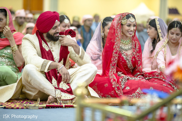 Indian couple smiling at ceremony.