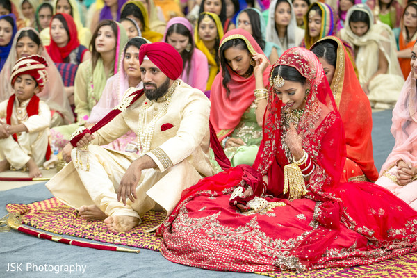 Maharani and Raja seating on the floor at sikh ceremony.