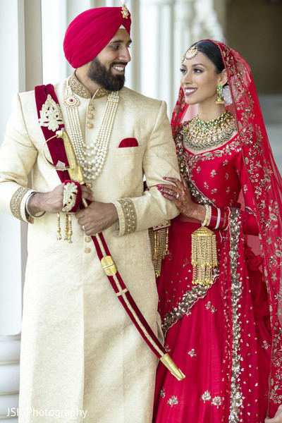 Indian bride and groom posing with their ceremony outfits.