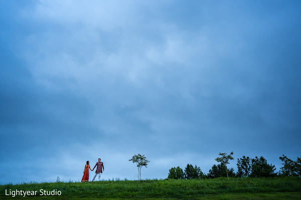 Lovely Indian bride and groom holding hands during outdoor photoshoot