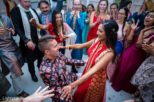 Cheerful Indian couple dancing during pre-wedding events