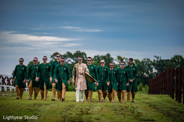 Groom accompanied by groomsmen during outdoor photoshoot