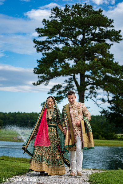 Bride and groom holding hands and smiling during outdoor photoshoot