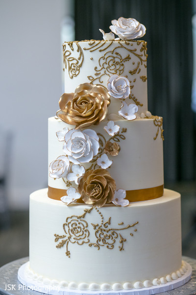 White and golden Indian wedding cake decorations.